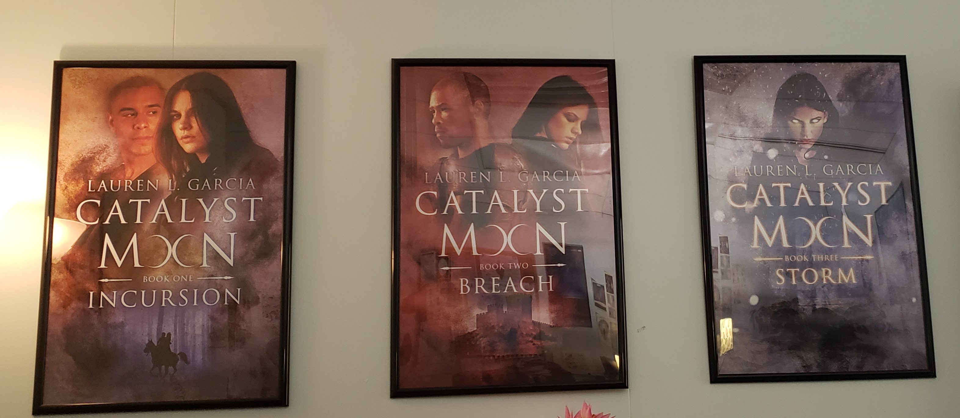Picture of all three Catalyst Moon book covers on a wall in the author's office.